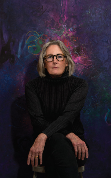Sigrid Burton sitting in front of her painting